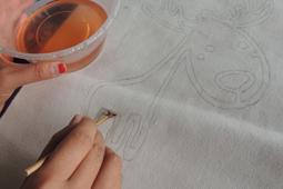 第三步上蜡,可以使用蜡刀等专业工具,也可以使用家里的棍子,勺子或筷子之类的工具,因为图案比较简单,不需要精细的描图。  描图的时候,要控制蜡的温度,熔化的蜡可以穿透布料,太热得话,不好描图,并且容易太稀薄。
